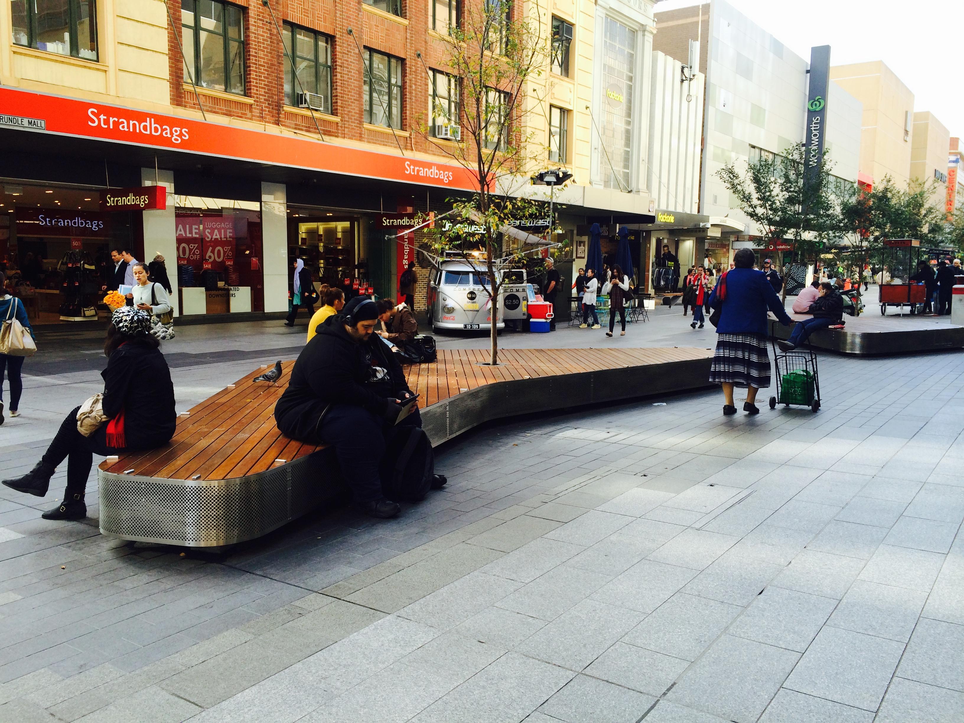常設のベンチで休憩する人々。ベンチがストリート上に点々と設置されている。