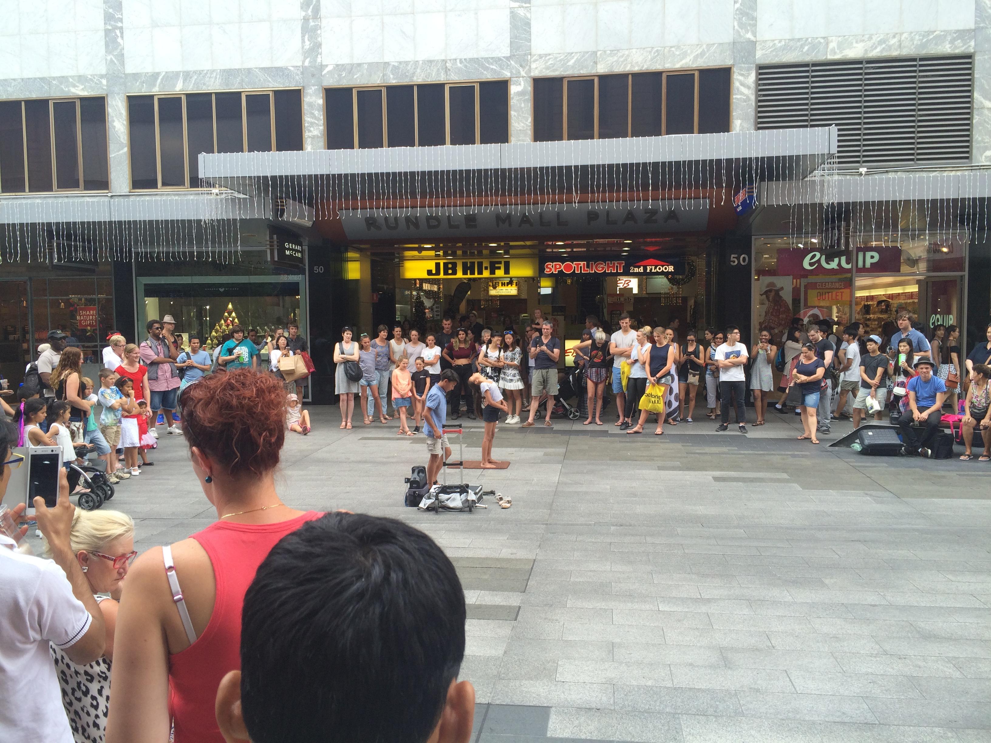 小学生の兄弟が通りいっぱいの観客にショーをしている。