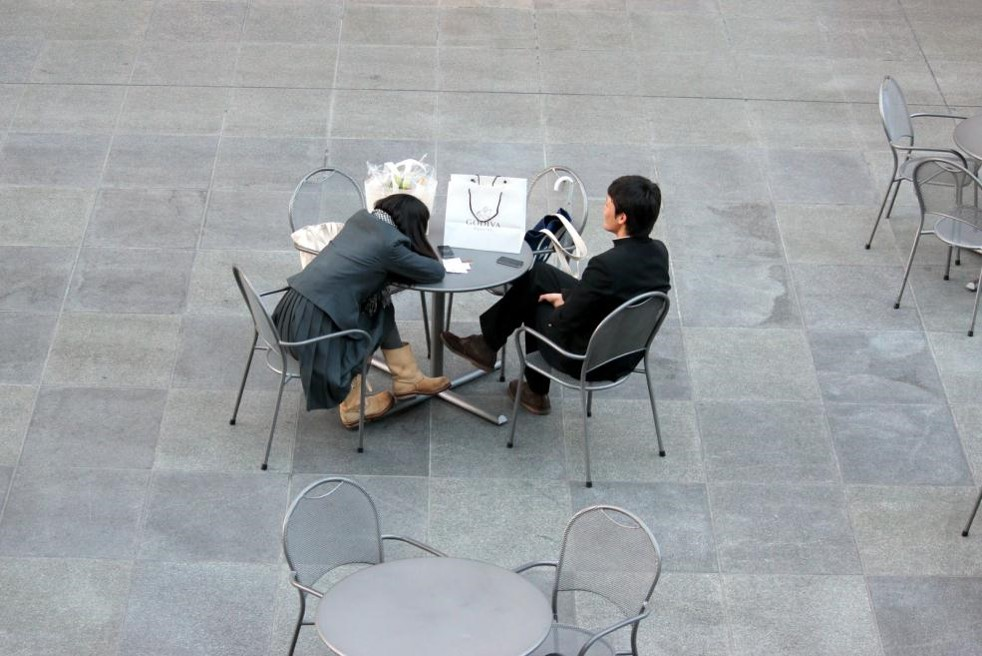 放課後、まちなか広場でデートする高校生