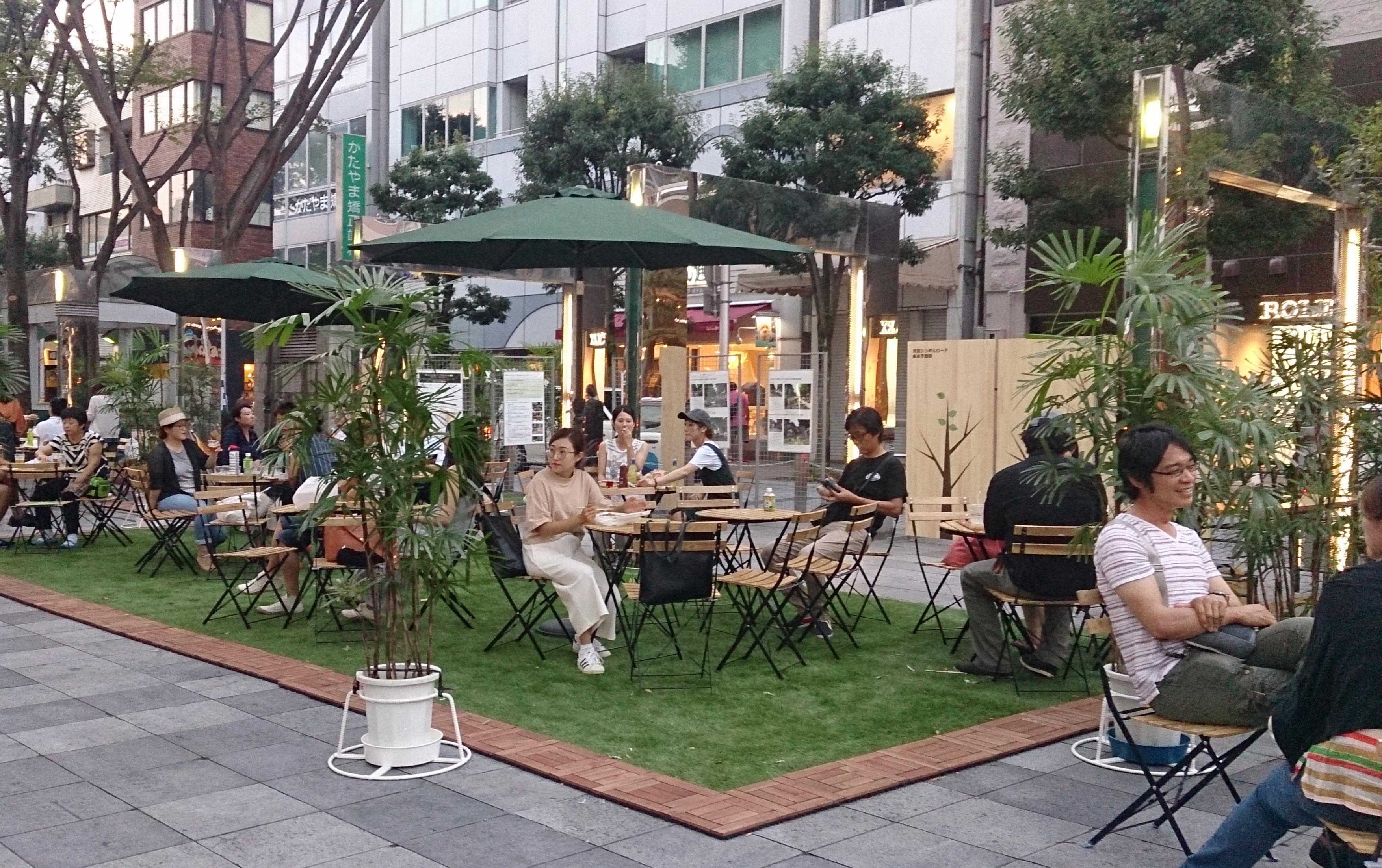 人工芝と木製の可動椅子・テーブルによる飲食空間